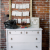 White vintage dresser for card table and guest book area. Large old frame with seating chart hanging from it.